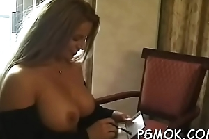 Delicious babe with huge bust poses for the camera whilst smoking